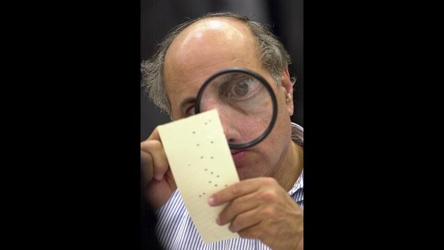 Broward County canvassing board member Judge Robert Rosenberg uses a magnifying glass to examine a disputed ballot Friday, Nov. 24, 2000, at th_186905
