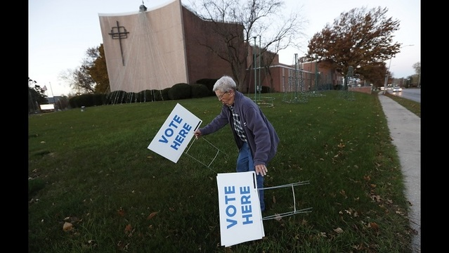 Precinct volunteer Roy Reese puts up signs outside of precinct 39 at the First Church of the Open Bible, Tuesday, Nov. 8, 2016, in Des Moines, _187652