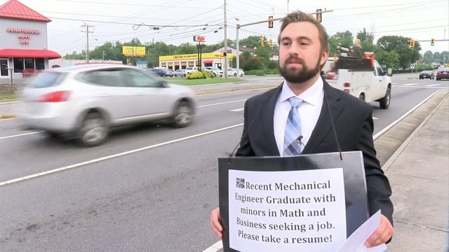 Local college grad seeking job hands out resumes at intersection